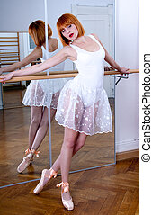 beautiful ballerina with a white tutu and red hair