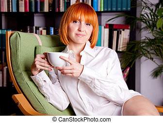 woman with red hair ist sitting on a chair and drinking coffee