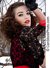 beautiful young woman outside in winter with dark hair and red lips