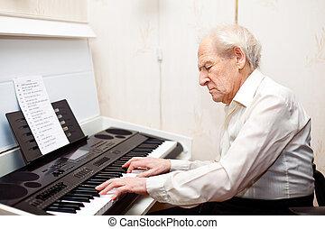 Senior Man Playing Piano - grey-haired senior man playing...