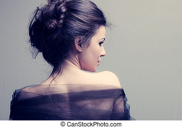 elegant woman with bun, back view profile, studio shot