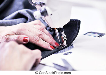 Hands of Seamstress Using Sewing Machine - woman Hands of...