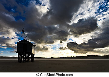 Boat house on the beach with dark cloudscape
