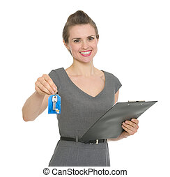 Smiling realtor holding clipboard and giving keys isolated -...