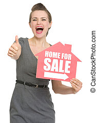 Happy realtor with home for sale sign showing thumbs up. HQ...