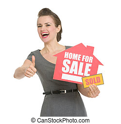 Happy realtor with home for sale sold sign showing thumbs...