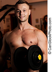 Man exercising his arm muscles by lifting two dumbell free weights in a fitness club.