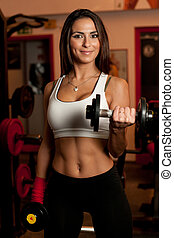 Girl in fitness club - Beautiful young woman working out in...