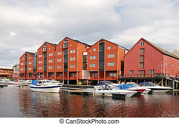 Restored warehouses on stilts over the river in Trondheim -...