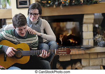 Young romantic couple sitting and relaxing in front of fireplace at home