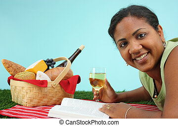 Woman on Picnic - Picnic Basket filled with food while woman...