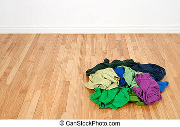Pile of colorful clothes on the wooden floor