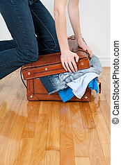 Woman trying to close suitcase with too much clothing -...