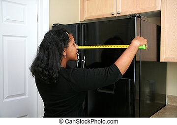 Moving In - Woman measuring in the kitchen