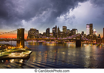 New York City Manhattan Panorama, view at night with office building skyscrapers skyline illuminated, U.S.A.