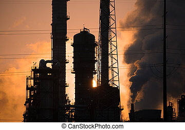 Oil Refinery at Sunrise - The run rises behind an oil...
