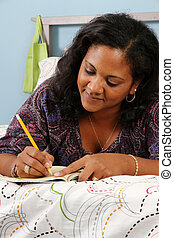 Woman On Bed Writing - Woman laying on a bed in bedroom