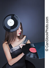 woman in black dress sitting with vinyl record - sexy model...