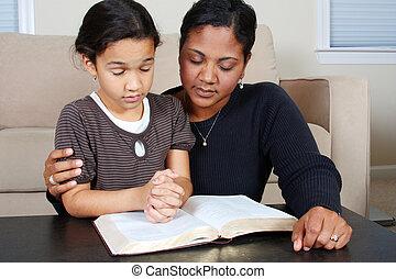 Praying - Minority woman and her daughter praying together