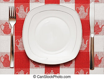 Knife, white plate and fork on red tablecloth