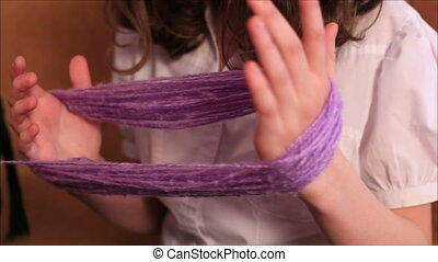 girl rewinds the yarn
