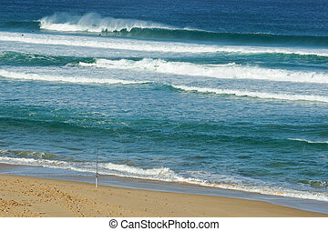Fishing rod and surfers - Swell and fishing rod set up at...