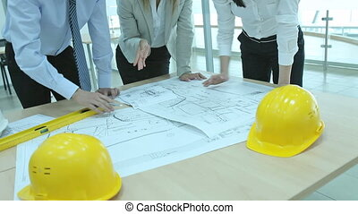 Team of architects working together, examining blueprints,...
