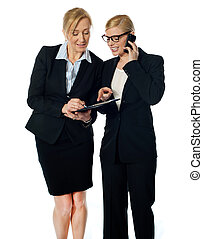 Two females looking at progress report and discussing One of...