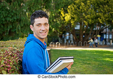 Student with Text book - Male student holding textbooks...