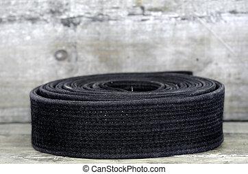 black belt - a black belt on wooden background