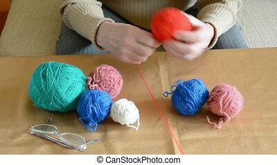 hands winding thread on a ball