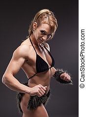Strong athletic woman body builder posing