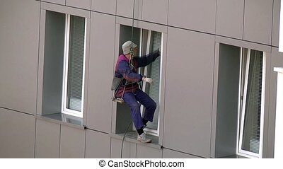 Window  cleaning - Man washes windows on a skyscraper