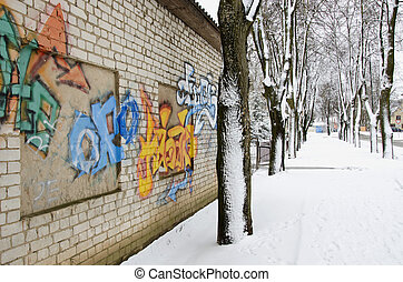 Walls graffiti and snowy lime tree trunk in winter -...