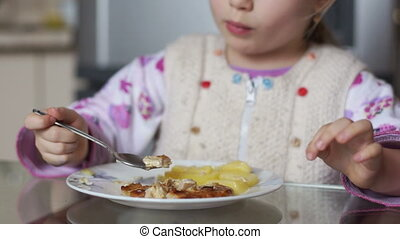 Child eating potatoes. Girl sitting
