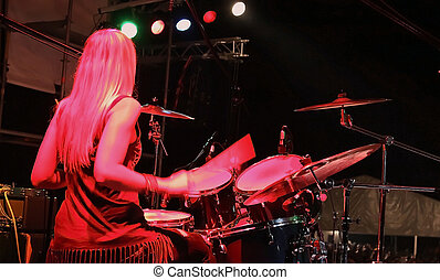 drummer girl live on stage under red lights