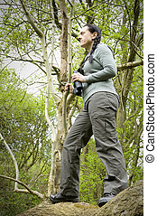 woman in tree using binoculars