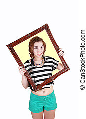 Girl holding picture frame.