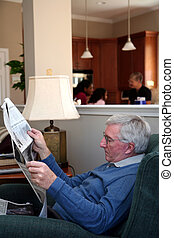 Man Reading Newspaper - Man sits and reads newspaper at home...
