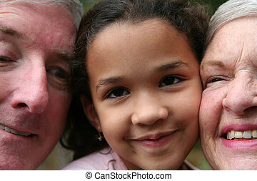 Grandparents with Grandaughter - Happy Senior Couple smiling...