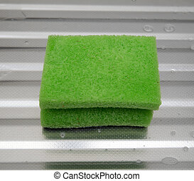 green sponge on a metal surface