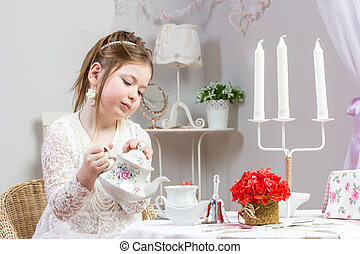 A beautiful little girl having a tea party
