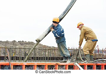 builder worker pouring concrete into form - builder worker...
