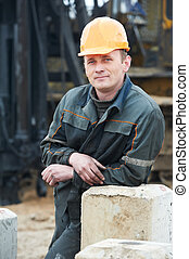 builder in dirty workwear at construction site - Smiling...