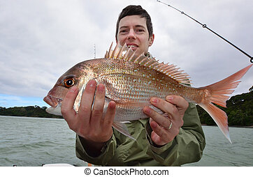Fishing - Watersport - A man holds a fish that he caught...