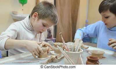 pottery - group of children decorating their pottery at clay...