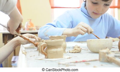 children brushing their pottery - group of children brushing...