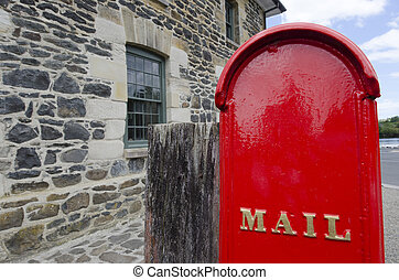 Post - Mail Service - An old red mail box in the street.