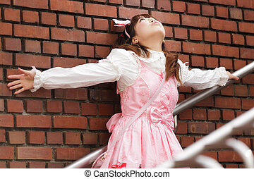 stressed japanese lolita leaning against brick wall on...