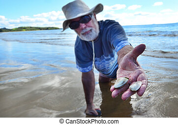 Food and Cuisine - Seafood - A man picks tuatua shellfish on...
